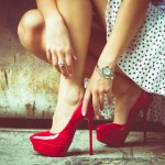 Woman-Putting-On-Red-High-Heels